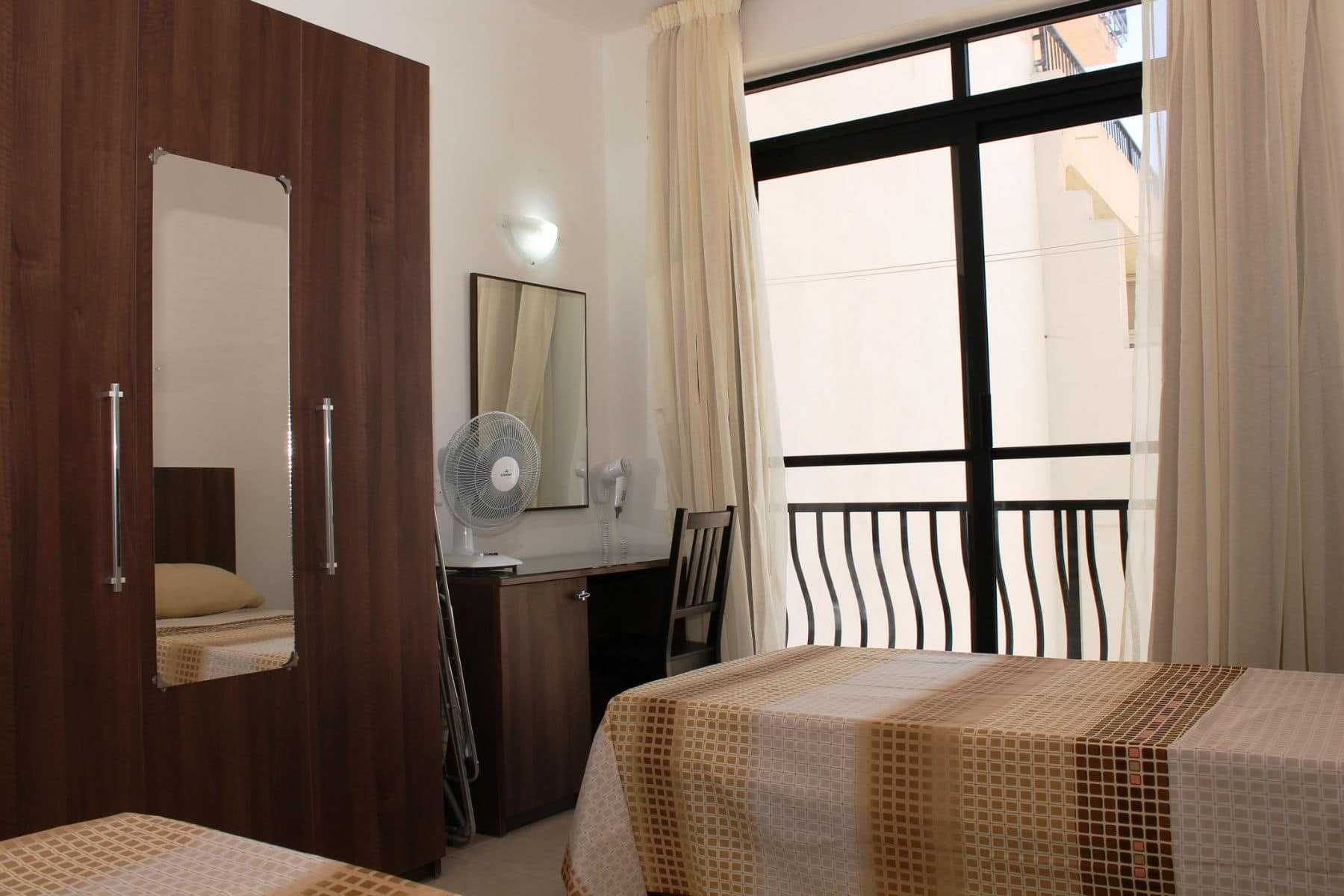 14. main bedroom with vainity desk and hair dryer. A small ...