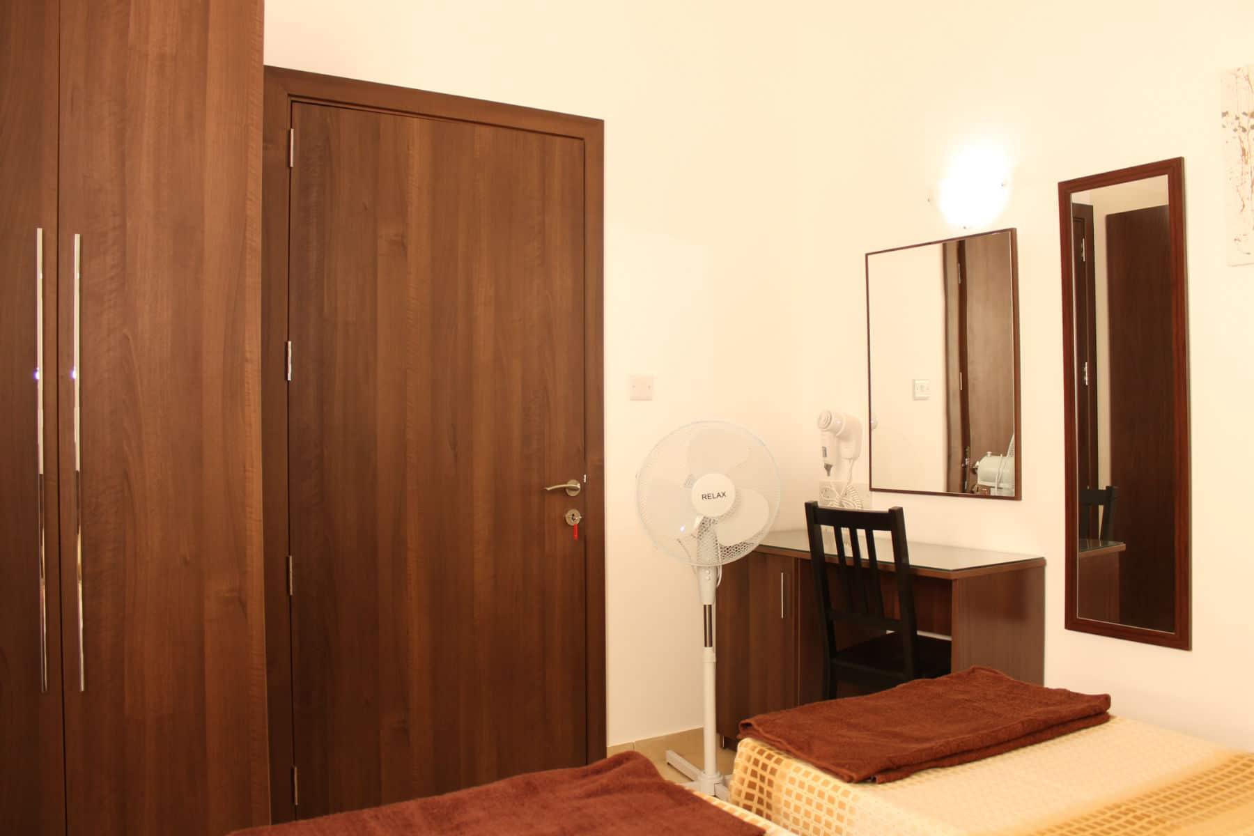 Main bedroom with waldrobe, vanity desk, fan and hairdryer ...